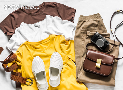 Women's clothing - three basic cotton t-shirts, sneakers, bag and loose trousers slouchy on a light background, top view