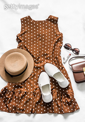 Summer brown polka dot sleeveless dress, white leather sneakers, cross body bag, sunglasses, lipstick and hat on a light background, top view