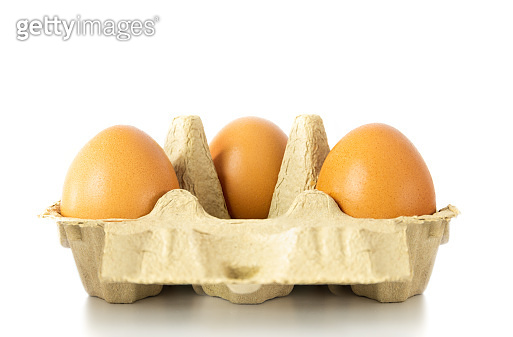 Three eggs in egg carton with distance social distancing isolated in white background.