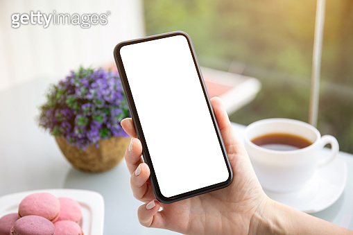 female hands holding phone with isolated screen in cafe