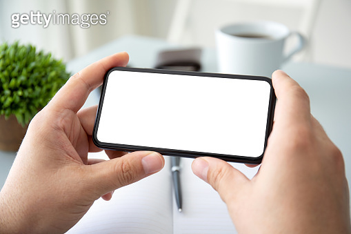 male hands holding horizontally phone with isolated screen in office