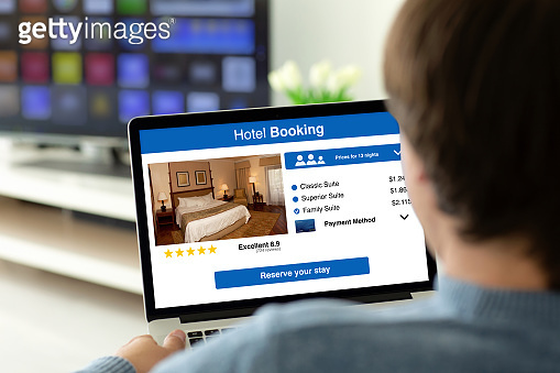 man holding laptop with app hotel booking on the screen