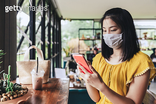 New normal of Traveler asian woman with mask using mobile phone in coffee shop