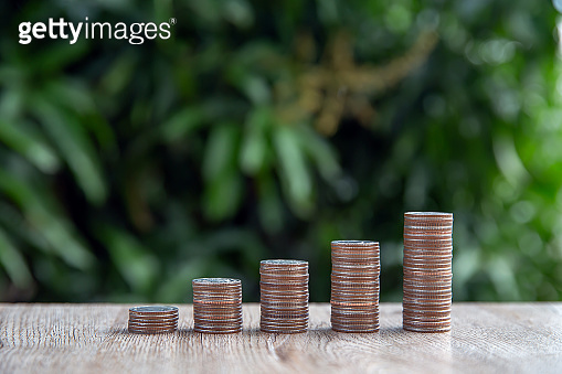 Many coins are stacked in a graph shape for money saving ideas and financial planning insurance.