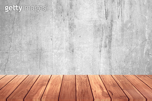 Wooden floor or shelf with raw old cement concrete or plaster wall with stains and cracks for background and blank template for displaying products.