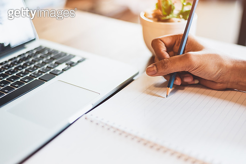 Close up of working woman hand using laptop computer and writing letter on notebook paper in office desk. Business and people lifestyles. Financial and Economy investment. Work from home concept