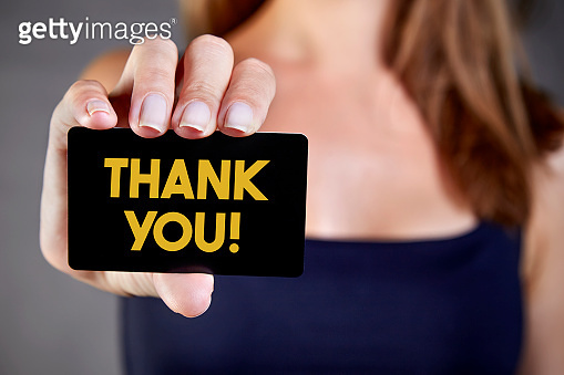 The woman is holding a card that says thank you.