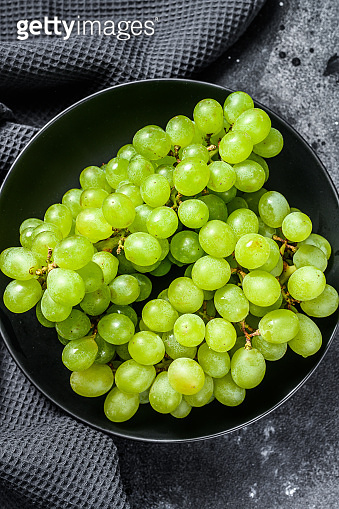 Green ripe grapes in a plate, fruits of autumn. Black background. Top view