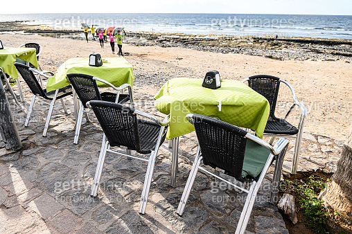 The tables of an outdoor cafe on the promenade by the ocean. 07.01.2020 Tenerife, Canary Islands