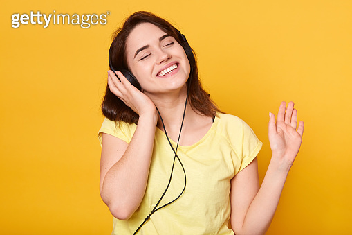 Indoor shot of happy relaxed woman with dark hair, wearing casual attire, posing with headphones, keeping eyes closed, enjoying listening to music, standing against yellow studio wall. Hobby concept.