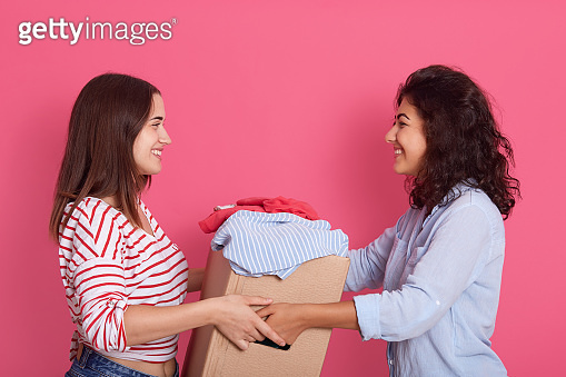 Indoor shot of two attractive women posing isolated over rosy background, smiling lady handing big carton box with clothes, young female gives charity clothing for poor people. Donation concept.
