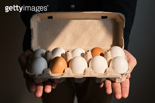 Cardboard boxes with chicken eggs. A man holds boxes with uncooked eggs. Natural organic farm product. Preparing for Easter holiday. Fresh food delivery, carton package. Raw ingredient for cooking eat