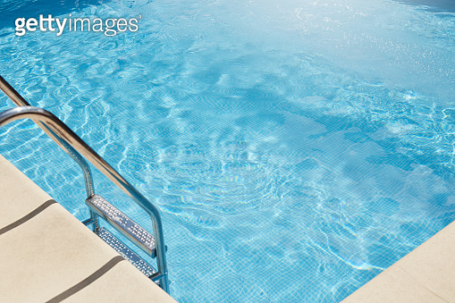 Top view of swimming pool with clear blue water, metal stairs into pool, no people inside, transparent water, sunlight, having sunny day, summer and rest conept, spa resort conditions. Rest concept.