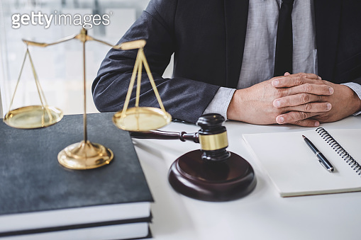 Male lawyer or judge working with contract papers, Law books and wooden gavel on table in courtroom, Justice lawyers at law firm, Law and Legal services concept