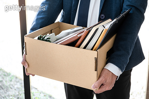 Images of businessman carrying packing up all his personal belongings and files into a brown cardboard box has frustrated and stressed to resignation and signing cancellation contract letter