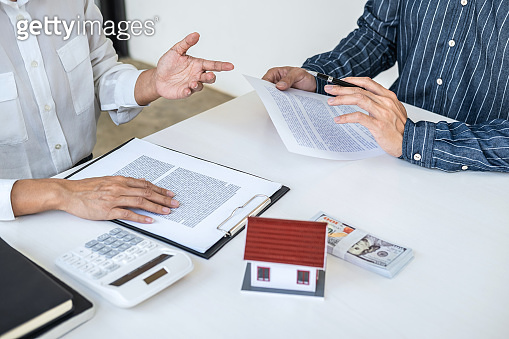 Real estate broker agent consult to customer to decision making sign insurance form and sending house model to client after approve, home model mortgage loan offer for and house insurance