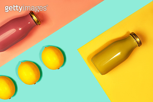 Bottles of multicolored juices or smoothies and lemon on yellow, pink coral and trendy mint green blue background.