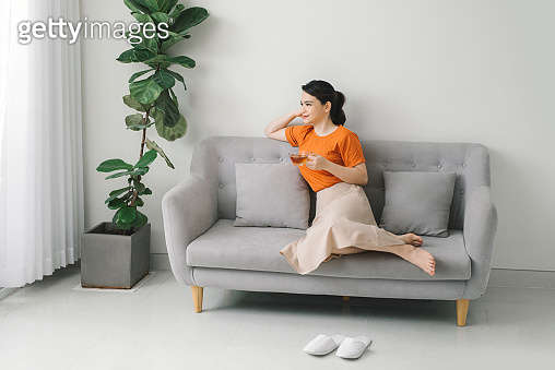 Attractive young woman drinking a cup of tea while relaxing on a sofa at home