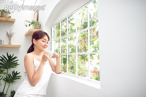 Asian woman in the morning holding a cup of tea or coffee and standing behind the window