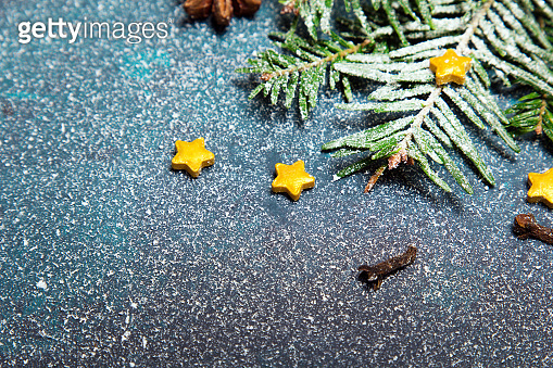 Beautiful Christmas background with decorations. Fir twigs and small yellow stars on dark background. Copy space for your text
