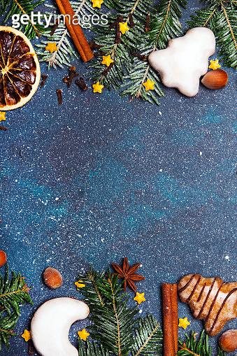 Christmas background with decorations with copy space for your text. Christmas cookies, gingerbread cookies, dried orange slices, spices and fir twigs on dark background.