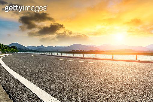 Asphalt road and mountain landscape at sunset.