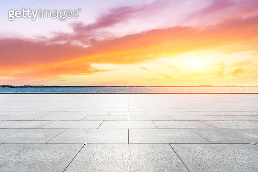 Empty floor and lake with dreamy clouds at sunset.