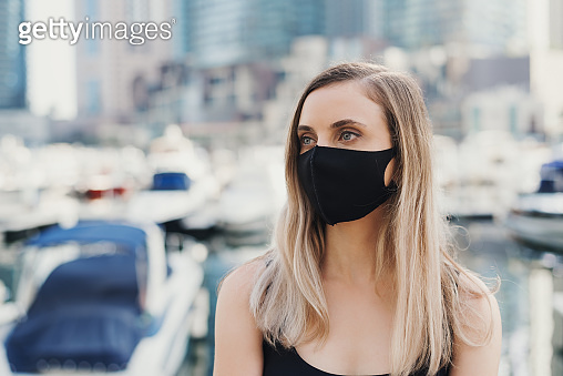 Close up portrait of a blond woman wearing protective face mask of black color at city street.  Social distance and new normal concept