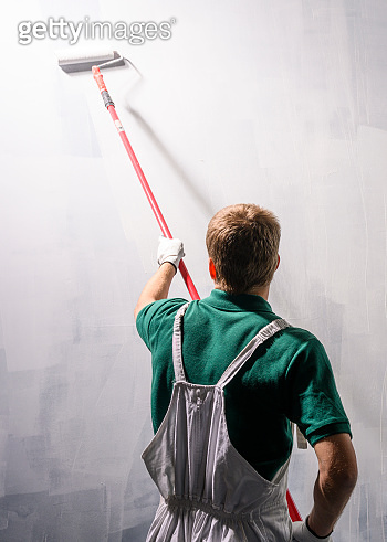 Male decorator painting a wall with white color.