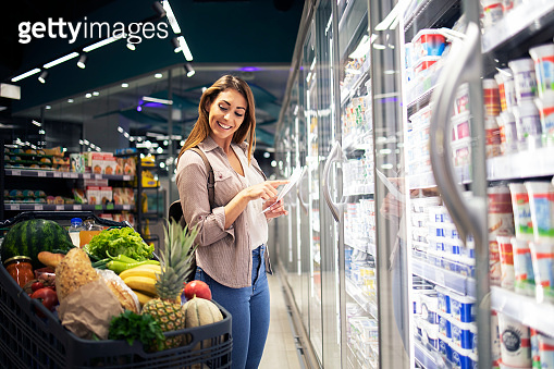 Woman with shopping list standing by the fridge in supermarket and checking cart. buying food for lunch.
