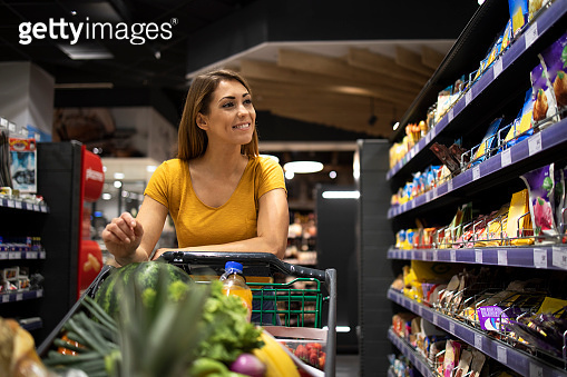 Woman shopping food in supermarket. Female person pushing cart and taking food from the shelves.