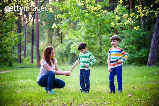 Young woman mother applying insect repellent to her two son before forest hike beautiful summer day or evening. Protecting children from biting insects at summer. Active leisure with kids