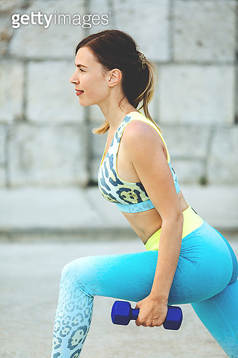Young beautiful woman squats with dumbbells.