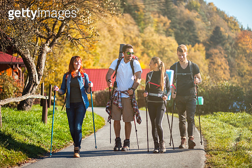 Group of friends hiking through countryside together