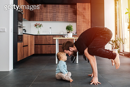 Father standing on his fingers next to his infant baby