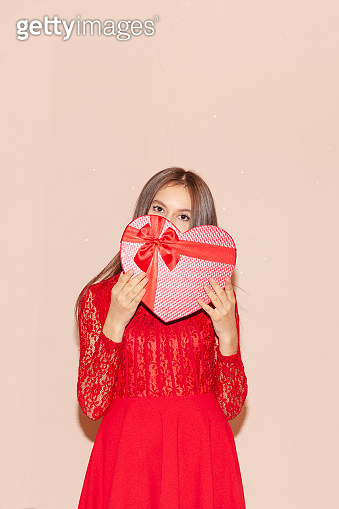 Happy young girl holds heart shaped giftbox. Valentines day, birthday, women's day, anniversary, holiday celebration concept