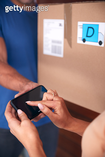 Close Up Of Woman Signing For Package Delivered By Courier On Mobile Phone