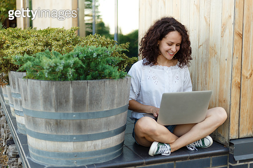Portrait of pretty curly woman sitting with legs crossed during summer day, working on the laptop smiling.
