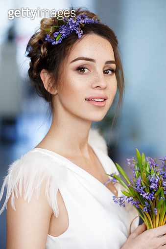 Beauty profile of a beautiful young bride with flowers in hairstyle, holding in her hands a bouquet of violete flowers.