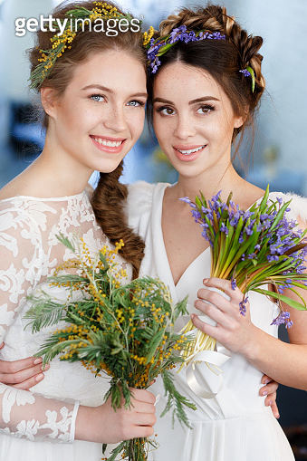 Vertical portrait of two brides in white wedding dresses with flowers in their hair, with a bouquet of wild flowers.