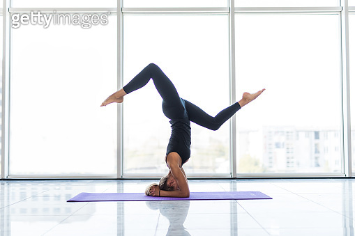 Beautiful young woman with sports smart watch working out indoors, doing yoga exercise on blue mat on panoramic window background