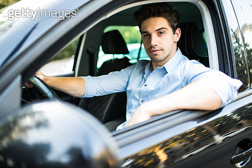 Concentrating on the road. Young handsome man looking straight while driving a car