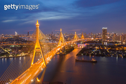 Aerial view of Bhumibol Bridge and Chao Phraya River in structure of suspension architecture concept, Urban city, Bangkok. Downtown area at night, Thailand.