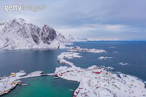 Aerial view of Norwegian fishing village in Reine City, Lofoten islands, Nordland, Norway, Europe. White snowy mountain hills, nature landscape background in winter season. Famous tourist attraction