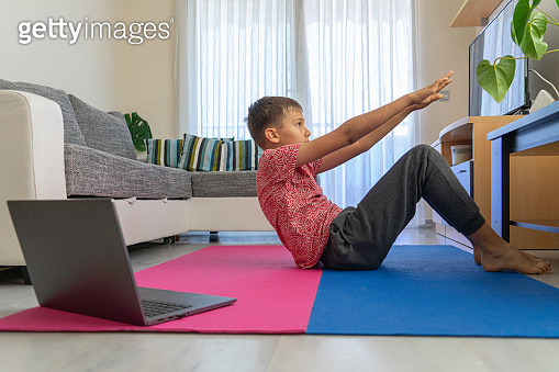 Teenager boy with laptop computer doing sport exercises, practicing yoga in the living room. Sport, healthy lifestyle, active leisure at home