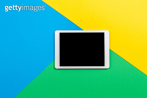 Digital tablet computer on light blue, green and yellow background. Top view