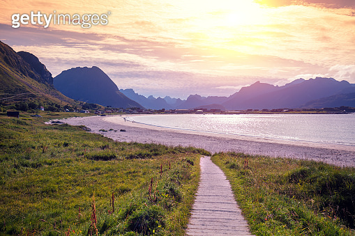 Fjord at sunset. Rocky beach in the evening. Beautiful nature of Northern Norway. Ramberg village and beach with white sand, Flakstad. Lofoten archipelago, Flakstadoya island. Norway