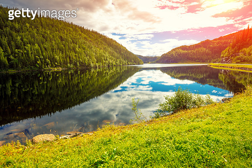 Rocky shore of a mountain lake on an autumn sunny day. Beautiful nature of Norway. Reflection on the lake