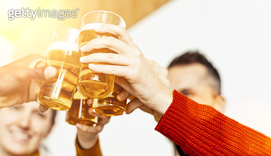 Group of friends enjoying a beer in brewery pub, Young people hands cheering at bar restaurant or at home, Friendship and youth concept image