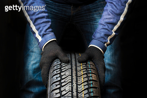 Hands of a mechanic in gloves hold a tire. Automobile mechanic with car tire. Car wheel replacement.